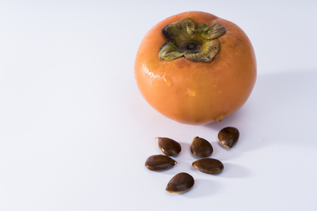 Persimmon fruit and seeds on white background