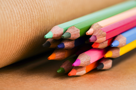 Colorful pencils on brown paper background