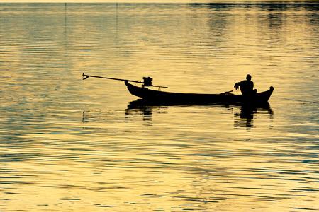 Fisherman in silhouette Stock Photo