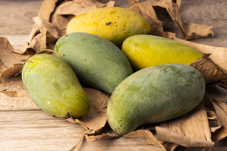 Green and yellow mango with dry banana leaves on wooden background