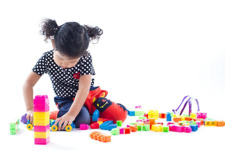 gar�on souriant: Une fille mignonne jouant des blocs de jouet sur fond blanc, vue en studio