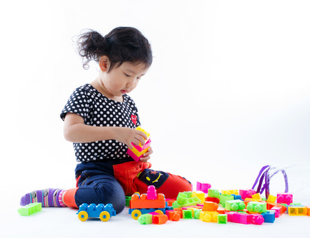 A cute girl playing blocks toy on white background, Studio Shot