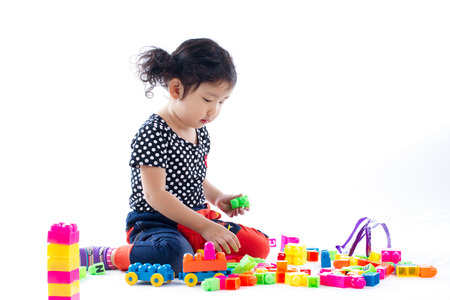 A cute child playing blocks toy on white