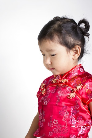 Cute girl wearing red Chinese suit on white background photo