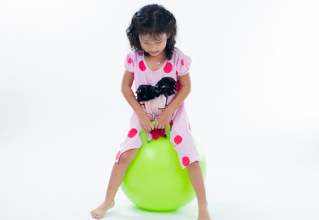 happy kid girl jumping on bouncing ball on white background photo