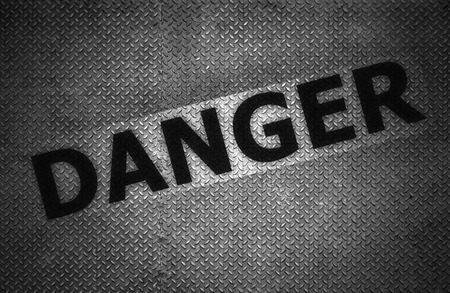 Steel plate background with danger text, Black and white. photo