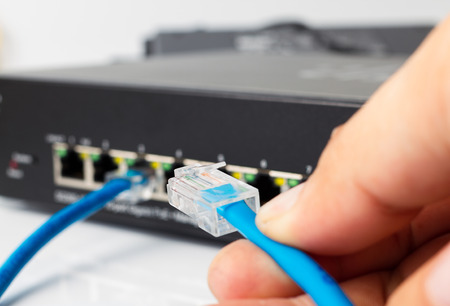 LAN network switch with ethernet cables plugging in on white Фото со стока