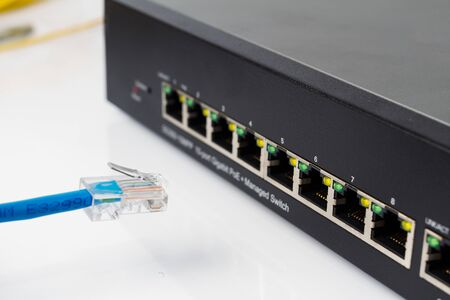 network switch: LAN network switch with ethernet cables plugging in on white Stock Photo