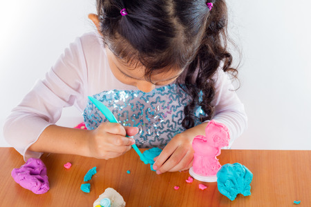 little dough: Little girl is learning to use colorful play dough on white background