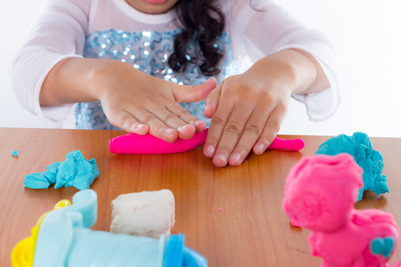 Little girl is learning to use colorful play dough on white background