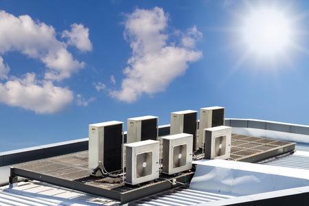air condition outdoor unit, on the roof with blue sky Фото со стока