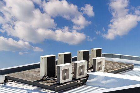 fresh air: air condition outdoor unit, on the roof with blue sky Stock Photo