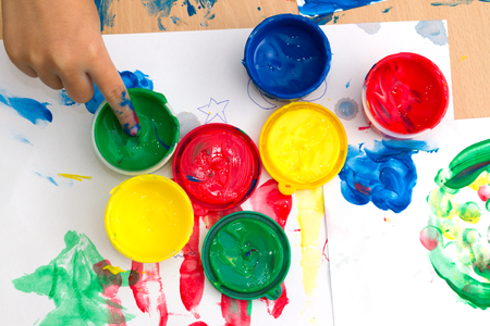 white colour: colorful finger paints with childrent hand on a table Stock Photo