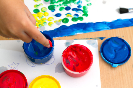 background people: colorful finger paints with childrent hand on a table Stock Photo