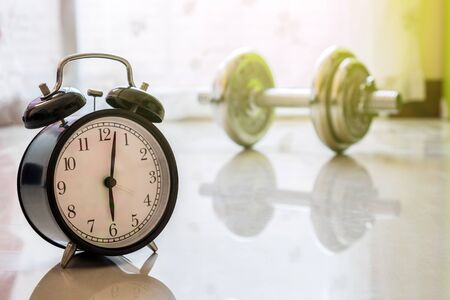 Best time to workout concept, clock and dumbbell background