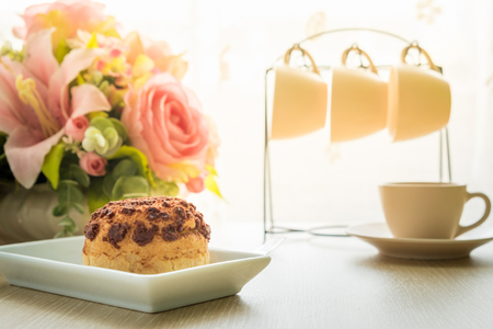 creampuff: Chocolate eclair and tea cup on white plate with flower and tea cup background. Chocolate cream puff cake.
