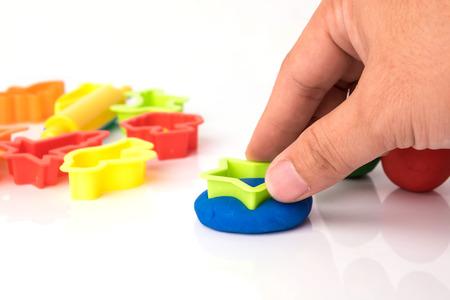 Hand cutting play dough via plastic block Stock Photo