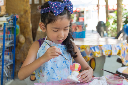 A cute asian girl painting color on the plaster statue.