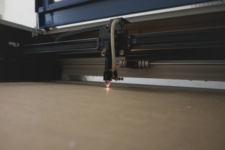 electric material: Laser cutting machine carving patterns on the plastic plate. Stock Photo