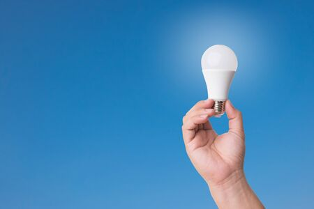 Hand holding LED Bulb with Lighting on blue sky background. Eco power concept.