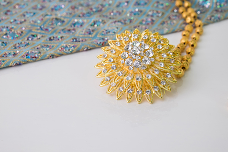 Close up shiny gold jewelry on white background with elegance fabric