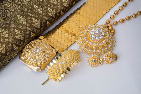Close up shiny gold jewelry on white background with elegance fabric.