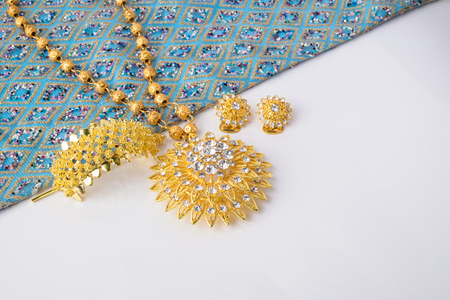 jewlery: Close up shiny gold jewelry on white background with elegance fabric