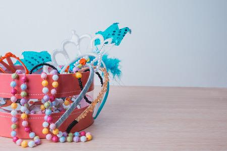 cintillos: Poco accesorios de niña estilo de vida establecido en una caja de color rosa. Bandas para la cabeza, collar, gafas en la mesa de madera. Foto de archivo