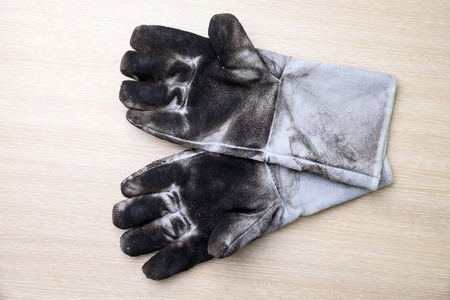 work gloves: Dirty leather gloves for industrial works on wooden background.