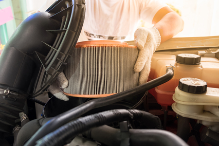 auto mechanic wearing protective work gloves holding a dirty, air filter over a car engine for cleaning Stock Photo