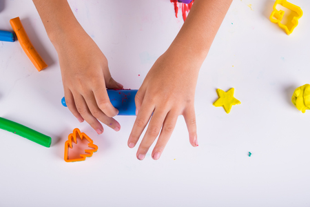 Little hand of kid learn to play coloful dough on white table