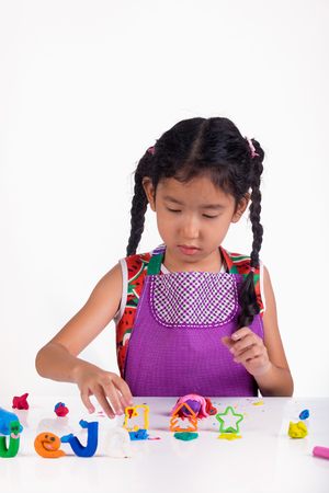 Little girl learn to play coloful dough on white table photo
