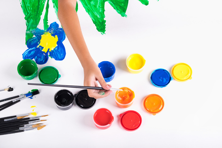 Little hand of kid learn to play colorful color on white paper