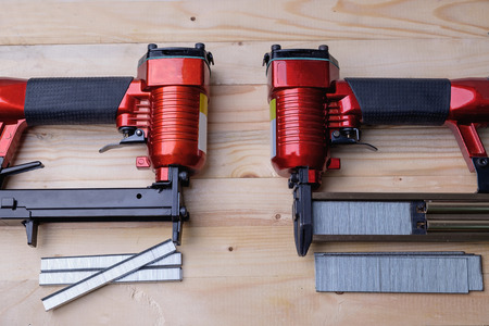 Close up pneumatic nailer gun on wooden background.