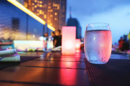 Drinking water in a glass on the dining table with ambient light
