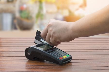 Gros plan d'un homme utilisant la machine EDC pour carte de crédit au comptoir de caisse Banque d'images - 88409640