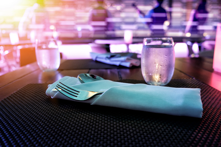 set of spoon and fork on a diner table with drinking water. Фото со стока