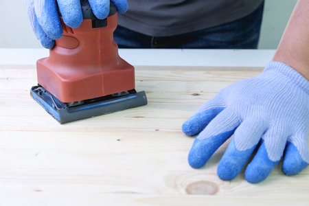 Carpenter using sander machine sanding on pine wood surface