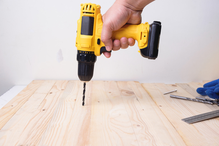Craftsman working with power drill on wooden plank Фото со стока