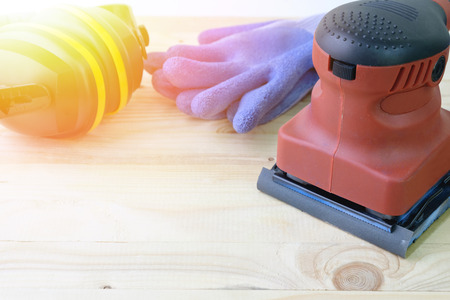 Close up orbital sander machine with protection equipment on wooden.
