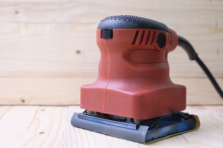 Close up orbital sander machine on pine wood table Фото со стока