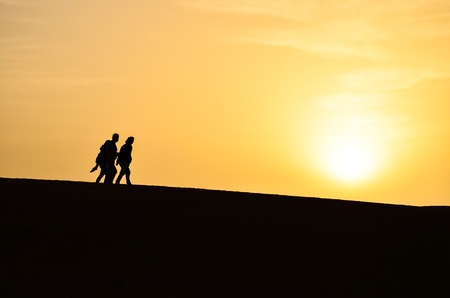 Silhouette of a Group of People Walking in the Sahara Desert During Sunrise