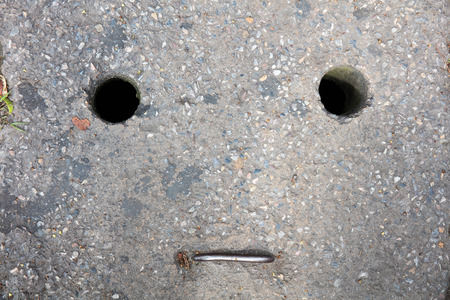 manhole cover: Face on manhole cover Stock Photo