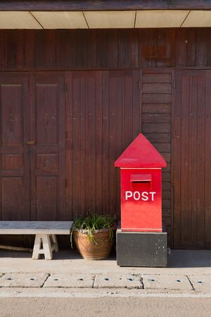 red post box: wooden wall and Red Post box on concrete floor
