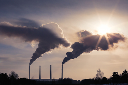 Smoking chimneys of industrial buildings complex. Against the sun