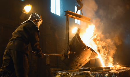 Worker controlling metal melting in furnaces. Workers operates at the metallurgical plant. Imagens
