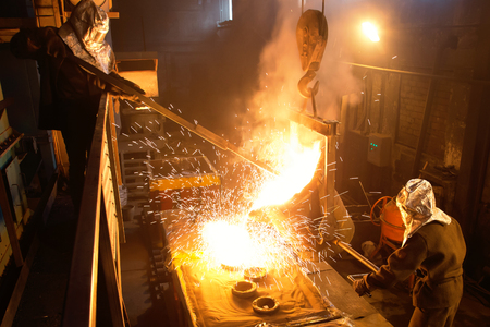 Workers operates at the metallurgical plant. Melting Iron in the foundry. Liquid metal in the factory, smelting iron and processing