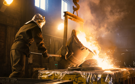Worker controlling metal melting in furnaces. Workers operates at the metallurgical plant. The liquid metal is poured into molds. Фото со стока