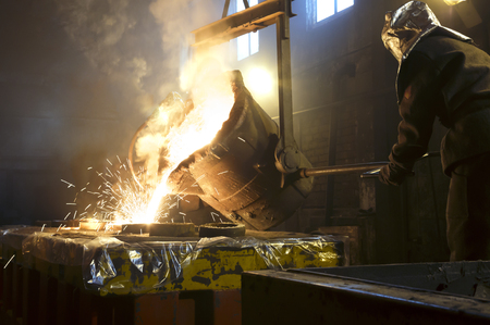 Worker controlling metal melting in furnaces. Worker operates at the metallurgical plant. The liquid metal is poured into molds.