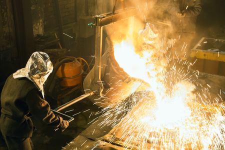 Worker controlling metal melting in furnaces. Workers operates at the metallurgical plant. The liquid metal is poured into molds